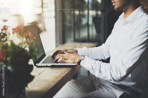 Fotografia  Close-up image of young professional businessman sitting at modern cafe and usin