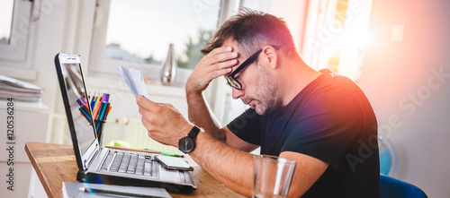 Fotografia Man reading letter and felling worried