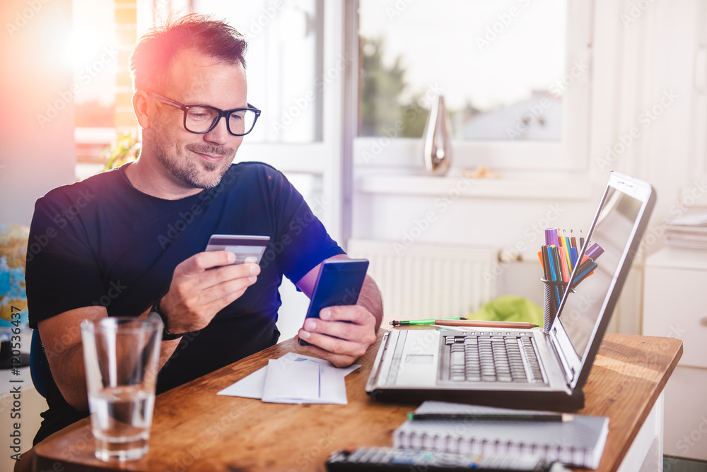 Fototapeta Businessman paying with credit card on smart phone