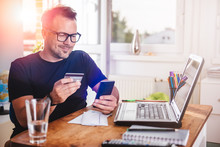 Businessman Paying With Credit Card On Smart Phone