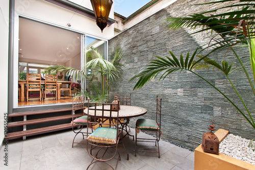 Staande foto Industrial geb. back yard with outdoor seating and barbecue with family