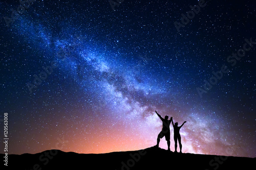 Poster Universe Milky Way. Colorful night sky with stars and silhouette of standing happy man and woman with raised up arms on the hill. Blue milky way with people on the mountain. Background with beautiful universe