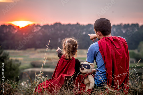 Fototapeta little girl with dad dressed in super heroes, happy loving family