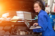 Young attractive woman mechanic working at the garage