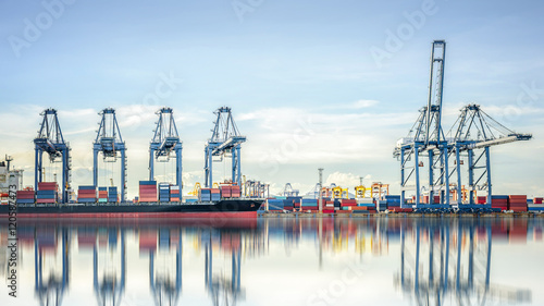 Fotografia International Container Cargo ship with working crane bridge in shipyard background, logistic import export background and transport industry
