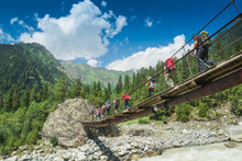Group Of Hikers Goes Above The Mountain River