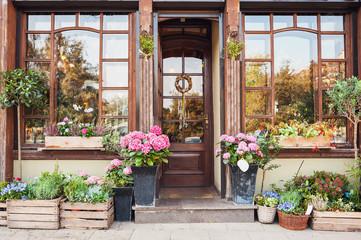 Cvjećarnica ili ulaz u kafić ukrašen cvijećem. Koncept rustikalnog stila. Prekrasni elementi dizajna