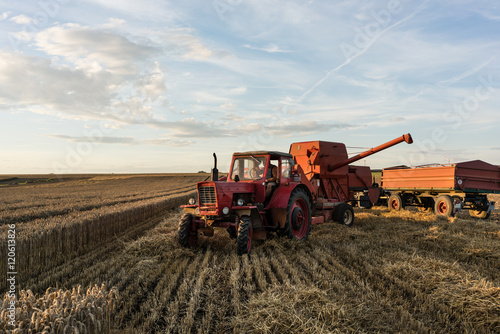 Farmer with his tractor and combine trailer finishing harvest day плакат
