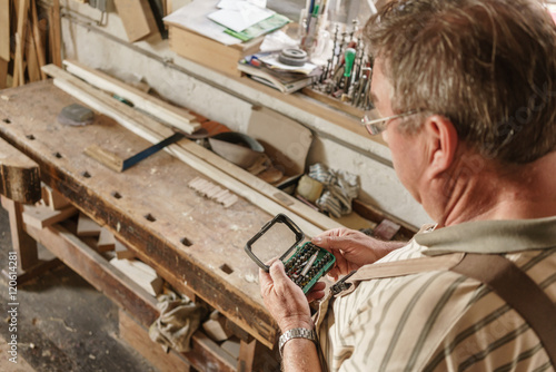 Carpenter at his wood workshop choosing bits for electric screwd