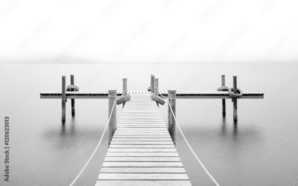 Wooden pier on the lake. Fog. Long exposure. Black and White.