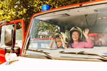Two Cute Kids Playing In Fire Truck, Pretending To Be Firefighters, Open Doors Day At Fire Station. Future Profession For Children. Educational Programme For Schoolkids