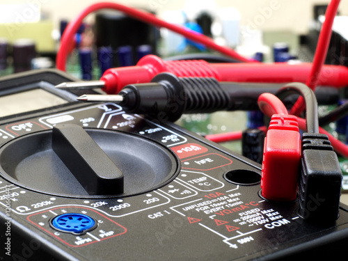 Fotografía  multimeter closeup with probes and circuit board in background, shallow depth of
