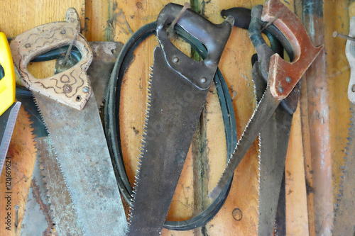 Fotografie, Obraz  old rusty hacksaw on the wall of the barn