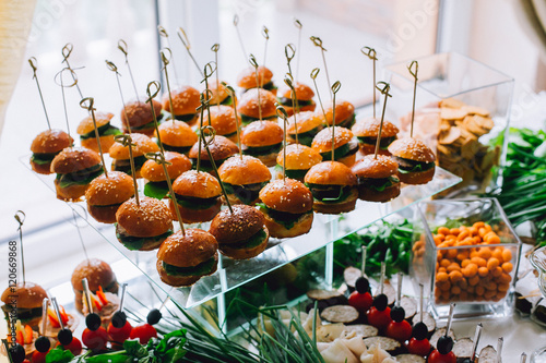 Poster Buffet, Bar Buffet table of reception with burgers, cold snacks, meat and salads