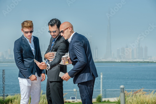 Photo  Three successful businessman looking at cell phone on the waterf