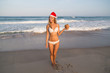 girl on the beach in Santa red hat New Year traveling vacation cocktail coconut