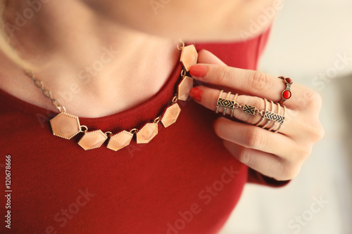 Foto  Female hand with beautiful accessories holding necklace, close up
