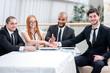 Businessman handshake. Four smiling successful businessmen sitti