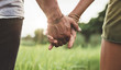 canvas print picture - Young couple holding hands in the field