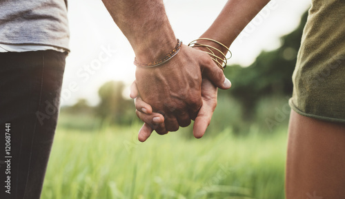 Cuadros en Lienzo Young couple holding hands in the field