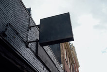Photo Blank Signboard On The Street. Black Square Signboard On The Black Brick Wall. Mock Up.