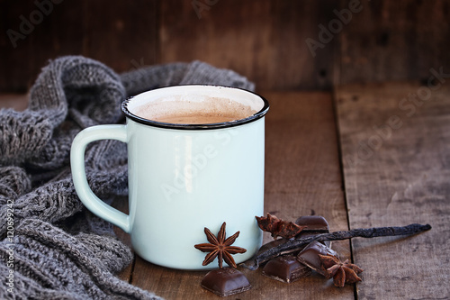 Spoed Foto op Canvas Chocolade Enamel cup of hot cocoa or coffee for Christmas with chocolate bars, vanilla pod, spices and gray scarf against a rustic background. Shallow depth of field with selective focus on drink.