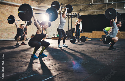 Adults lifting large barbells in fitness class