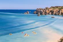 Canoes In The Turquoise Water Of The Atlantic Ocean Surrounding Praia Dona Ana Beach, Lagos, Algarve, Portugal