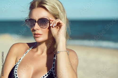 Portrait of a gorgeous blond lady in mirrored sunglasses and swimwear on the beach. Eyewear concept. Close up. Copy-space.