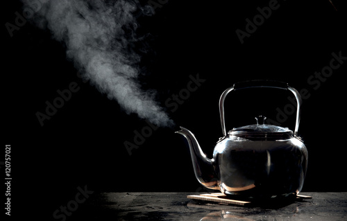 Fotografering  Tea kettle with boiling water on a black background