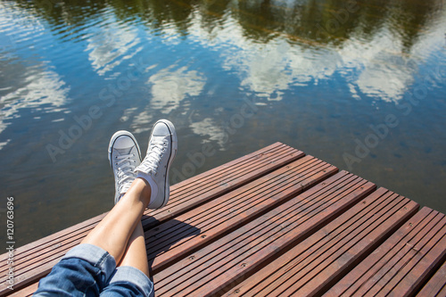 Fotografie, Obraz  Young girls feet relaxing by a lake.