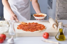 Woman Adding Tomato Sauce On Pizza