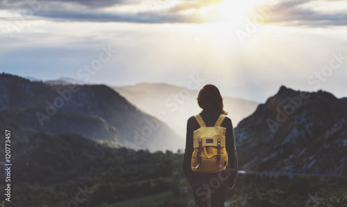 Obraz Hipster young girl with bright backpack enjoying sunset on peak of foggy mountain. Tourist traveler on background valley landscape view mockup. Hiker looking sunlight flare in trip in northern spain - fototapety do salonu