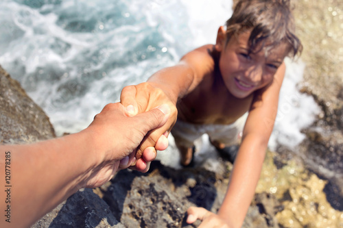 Fotografie, Obraz  boy helped by a friend to climb an inaccessible cliff