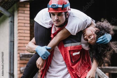 Fototapeta Rescue worker carrying disater victim