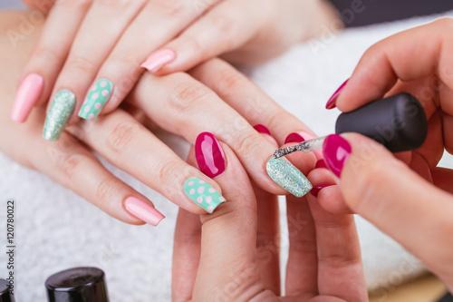Manicure - Beauty treatment photo of nice manicured woman fingernails. Very nice feminine nail art with nice pink and light green nail polish. Polka dots design.