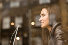 Window View Of Young Businesswoman With Laptop In Cafe