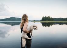 Woman Carrying Coton De Tulear Dog At Lake, Orivesi, Finland
