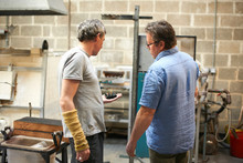 Glassblowers In Workshop Looking At Object