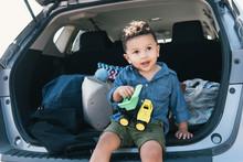 Male Toddler Sitting On Car Bo...