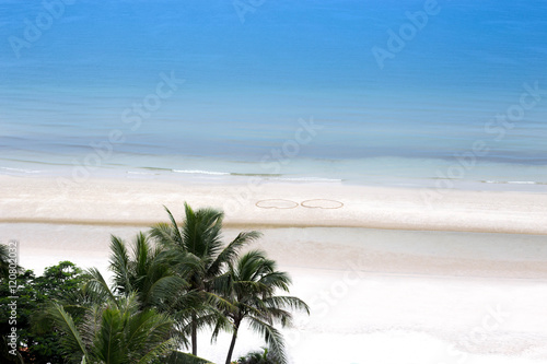 Spoed Fotobehang Eiland Coconut tree and ocean with love heart shape in the sand on the