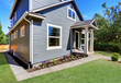 American house exterior with blue siding trim and small concrete floor porch