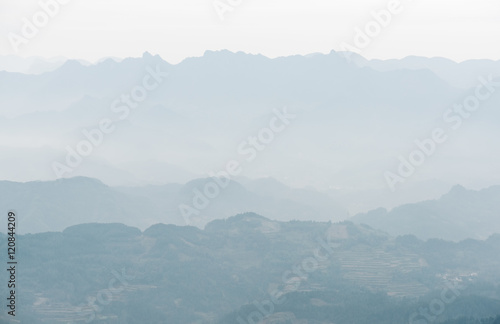 Aluminium Prints Blue Background of haze-shrouded mountains. View of mountains in mist