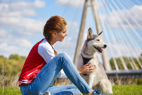 Spoed Fotobehang Kangoeroe Photo of woman with a dog in a grass field