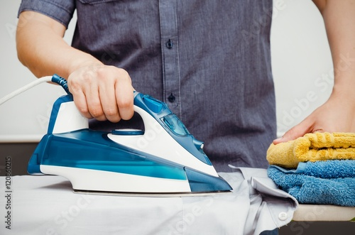 Stampa su Tela Man irons clothes on ironing board with blue iron