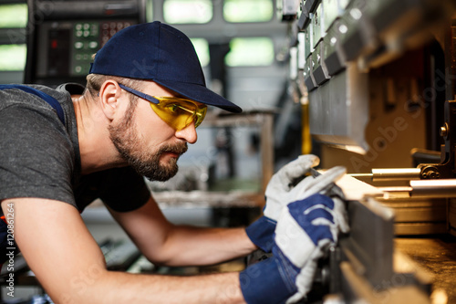 Portrait of worker near metalworking machine, steel factory background.
