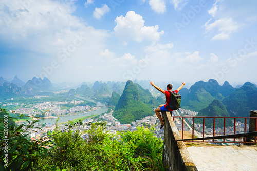 Hiker sitting on the top of hill with raised hands and enjoing view on the valley with city and mountains. Yangshou, China.