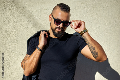 Photo  Portrait of sexy man in sunglasses holding on side of the glasse