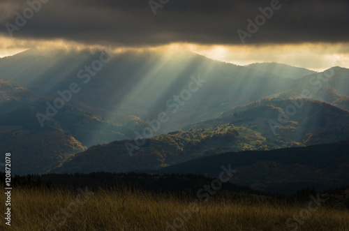 Foto op Canvas Olijf Heavy overcast sky with sunrays over meadows and colorful forests at autumn, mountain Goc, Serbia