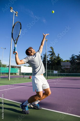Professional tennis player is doing a kick tennis on a tennis court on a sunny summer morning. The is dressed in sportswear.